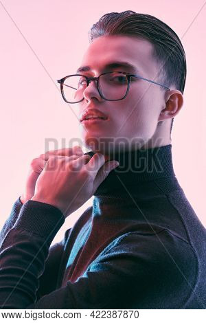 Glasses style. Portrait of a serious handsome man in classic glasses looking at camera. Men's accessories, optics. Business style.