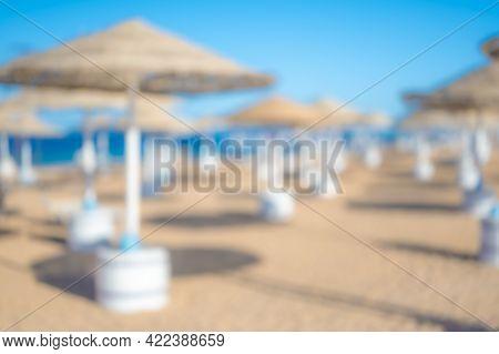 Blurred Blue Sea And White Sand Beach With Parasol, Beach Chair. Blurred Beach Umbrella Background.