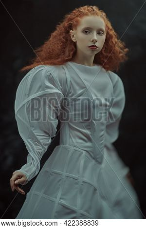High fashion art. Sophisticated female model with lush red curly hair posing in a white art dress. A studio portrait on a vintage background.