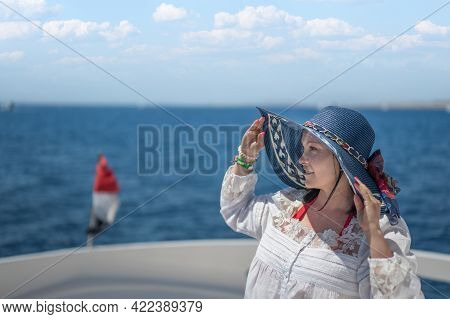 Woman In Wide-brimmed Hat Sits On Deck Of Luxurious Speed Boat On Background Of Sea. Woman In Wide-b