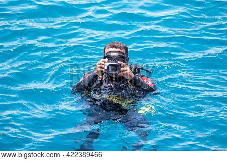 Underwater Photographer Videographer Scuba Dives On Surface Of The Sea. Underwater Photography And V