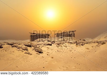 Small Huts In The Middle Of The Desert With An Amazing Landscape Background. Desert Stone Hut Under