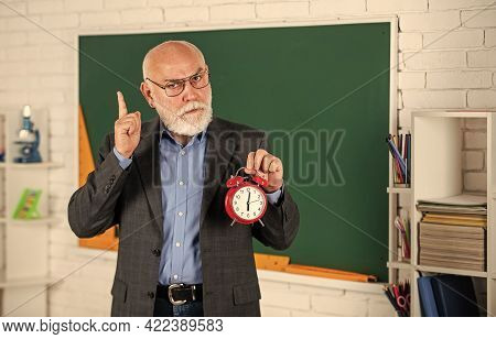 Time To Study. Discipline And Punctuality. Senior Teacher Hold Alarm Clock. Time Management. Begin O