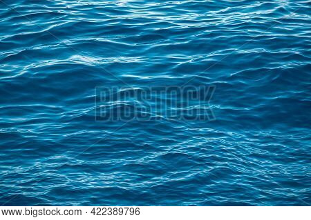 Blue Water Surface With Bright Sun Light Reflections, Water In Ocean Or Sea Background Closeup. Blue