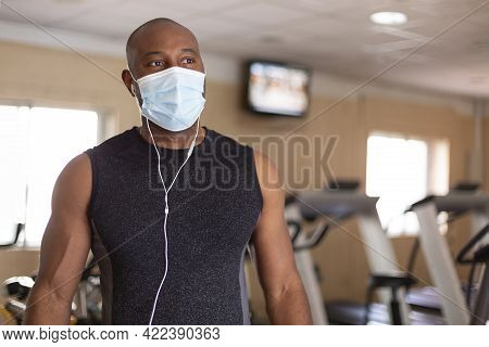 Portrait Of Young African American Man In Sportswear. He Is In The Gym And Wearing A Medical Mask As