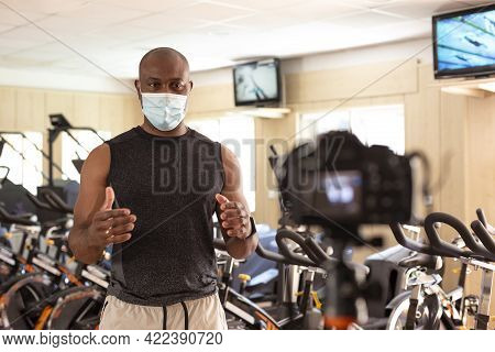 Male Sports Instructor In Gym With A Face Mask Recording Video Content For Online Classes, Streaming