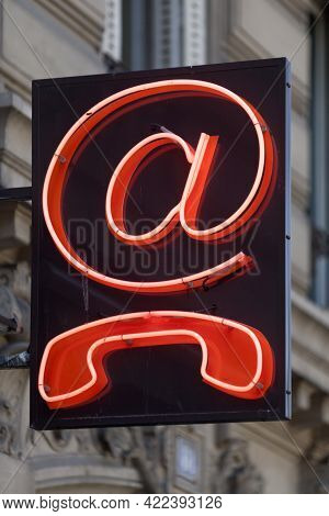 Outdoors Red Neon Sign Shaped Into An @ And A Phone.