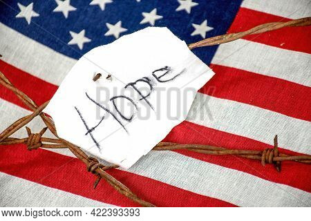 Hope Text On Torn White Fabric On Rusty Barbed Wire Fence With American Flag Background