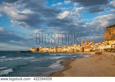 Cefalu cityscape at sunset in province of Palermo, Sicily, Italy. Medieval sicilian town Cefalu. Old town Cefalu and Cathedral Basilica in sunset light