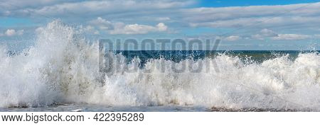 Panoramic View Of A White Foamy Waves With Blue Cloudy Sky Background
