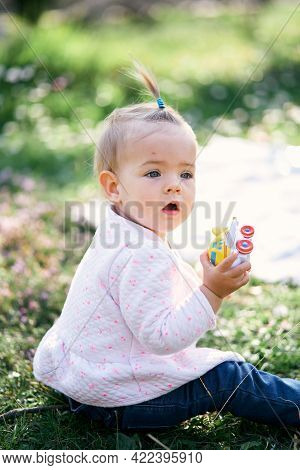 Pensive Little Girl With A Ponytail On Her Head Sits On A Green Lawn Among Flowers And Holds A Yello