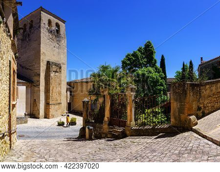 Narrow Old Town Street And Woman Walking Next To A Public Garden. Sepulveda Castilla.