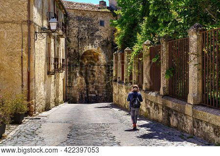 Narrow Old Town Street And Woman Walking Next To A Public Garden. Sepulveda. Castilla.