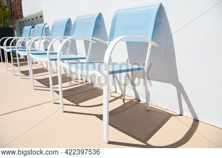 Outdoor Lounge Chairs. Blue Patio Chairs At Sunny Wall. Patio Or Poolside Furniture For Leisure