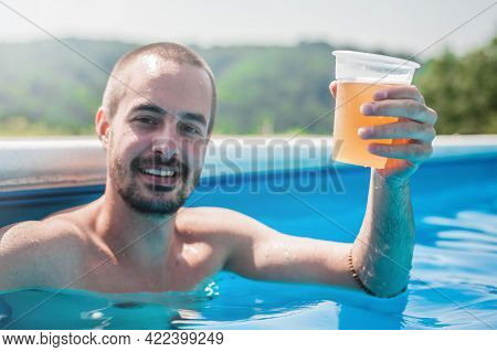 Happy Young Man Drink Beer And Enjoying In Swimming Pool