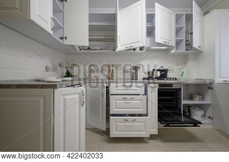 Luxury modern white kitchen showcase interior with furniture drawers pulled out and doors open