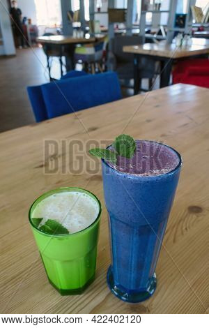 Blueberry And Banana Milkshakes With Mint Leaves On A Wooden Table In A Cafe