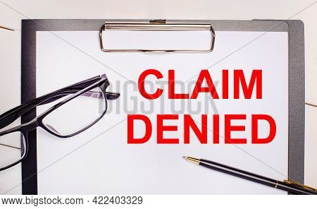 On A Light Wooden Background Glasses, A Pen And A Sheet Of Paper With The Text Claim Denied. Busines