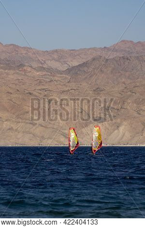 Eilat, Israel - May 24th, 2021: Two Wind Surfers Off The Shore Of Eilat, Israel, With The Jordanian