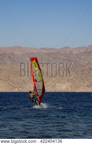 Eilat, Israel - May 24th, 2021: A Man Windsurfing Off The Shore Of Eilat, Israel, With The Jordanian