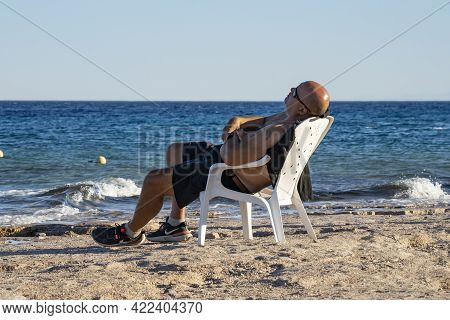 Eilat, Israel - May 24th, 2021: A Man Relaxing In A Plastic Chair On An Eilat, Israel, Beach, On A C