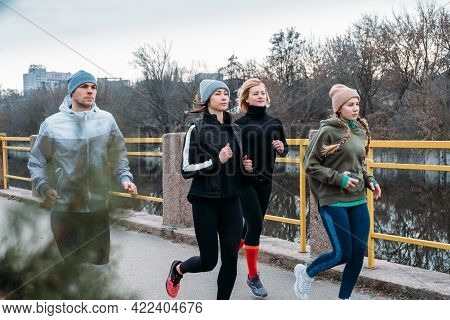 Young And Middle Aged Sports People Group Running In The Urban Environment. Group Of Runners In The