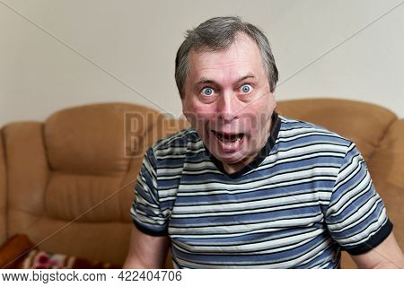 Elderly Freak Making Faces While Sitting On The Couch Looking At The Camera. Expressing Emotions