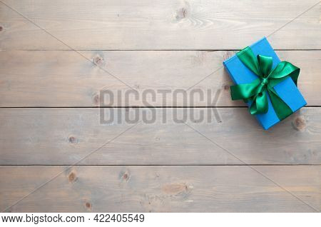 Blue Gift Box Wrapped With Green Silk Ribbon On A Wooden Table Background