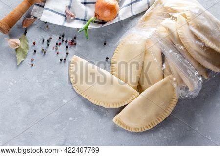 Frozen Semi-finished Products In The Bag On Grey Table. Russian Dumplings. Meat Dumplings, Ravioli.