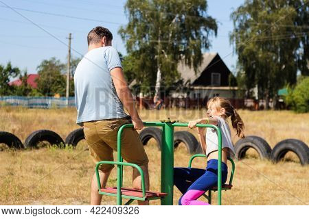 Defocus Little Preteen Girl Riding A Carousel On Playground With Young Man, Guy, Her Older Brother O