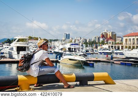 Sochi, Russia, July 27, 2019: Traveler Man With A Backpack On His Back Sits On The Dock And Looks At