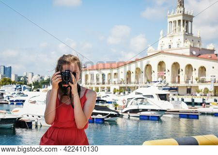Sochi, Russia, July 27, 2019: A Girl In A Red Photograph Looks At Us Through The Camera Nikon, Behin
