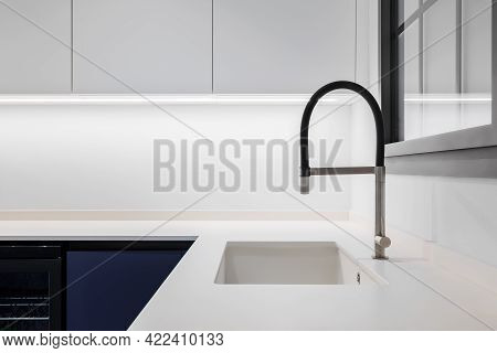 Black Faucet With A White Sink In A Stylish Modern Kitchen. Minimalism In Refurbished Apartment.