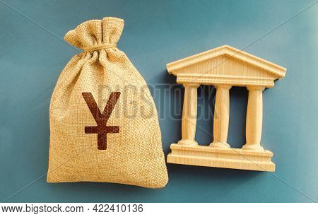Yen, Yuan Money Bag And Government Building. Business And Finance Concept. Deposit, Loan And Investm