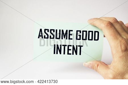 Assume Good Intent, Card Is Held By Female Hand On White Background. Good Intentions On Sticker, Pos