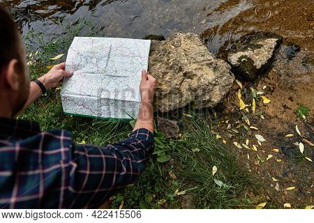 Stylish Hipster Traveler Exploring Map, Placing It On A Rock By The River. The Concept Of Hiking Tri