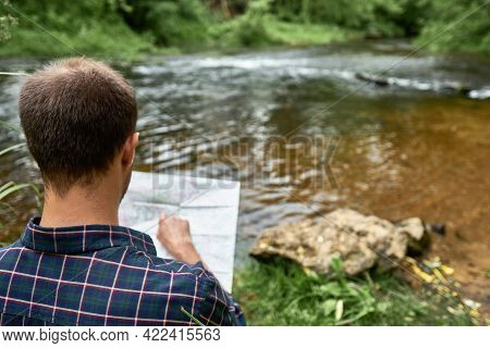 The Man In A Plaid Shirt Standing On The Bank Of The River Points A Finger To A Place On The Map. Th