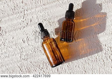 Glass Bottle Of Mineral Beauty Oil With Dropper For Skin, Hair. Product Packaging Serum On A White B