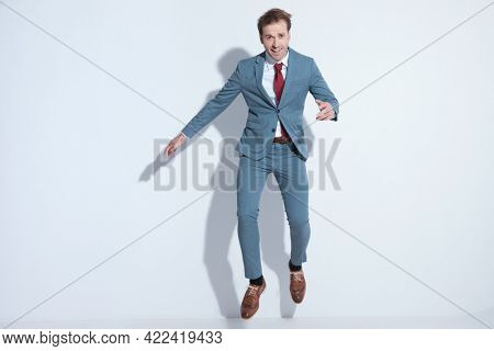 full body picture of enthusiastic young businessman in elegant blue suit jumping in the air and having fun while posing against gray background in studio