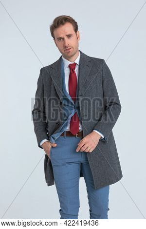 handsome businessman sticking one hand in pocket and posing with attitude