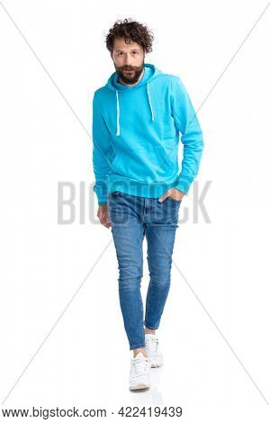 handsome young casual man holding hand in pocket and walking isolated on white background in studio, full body