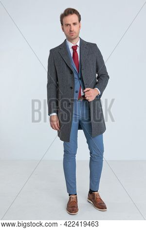 classy businessman wearing a nice suit with red tie is fixing his coat and looking at the camera