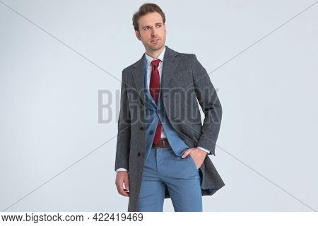 elegant handsome businessman sticking one hand in pocket and looking away in a fashion pose