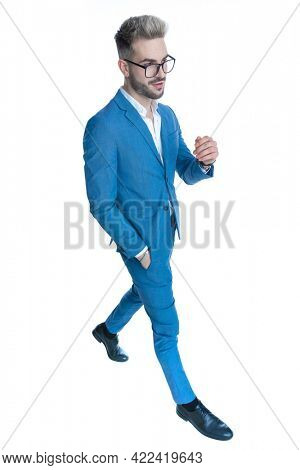 side view of full body picture of sexy elegant businessman in suit holding hand in pocket, smiling and walking isolated on white background in studio