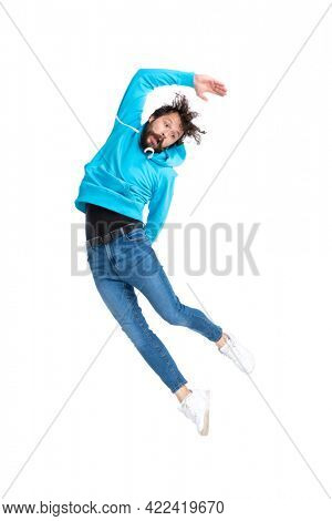 young casual guy in blue sweatshirt bending to side while leaping up in the air, being crazy and having fun while posing against white background in studio