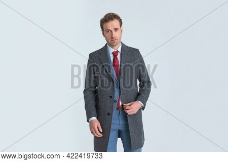 young businessman wearing a nice blue suit and coat and posing with classy vibe