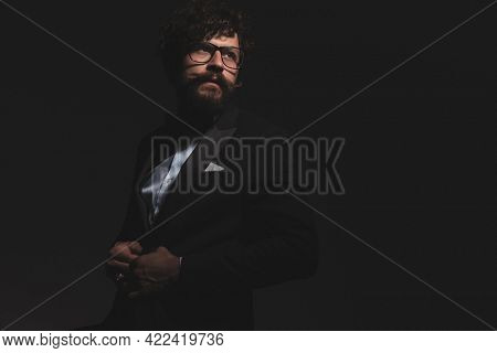 young handsome businessman closing his tuxedo, looking away and wearing glasses on gray background