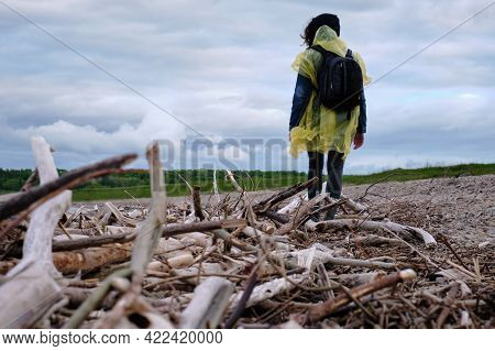 Woman With Backpack Standing On The Riverbank. Near The Branches Of Trees