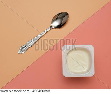 milk yogurt with metal spoon top view on pink background