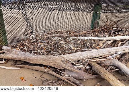 Driftwood Piled Up Against A Netted Swimming Enclosure Washed Up Due To High Tides And Erosion Of Th